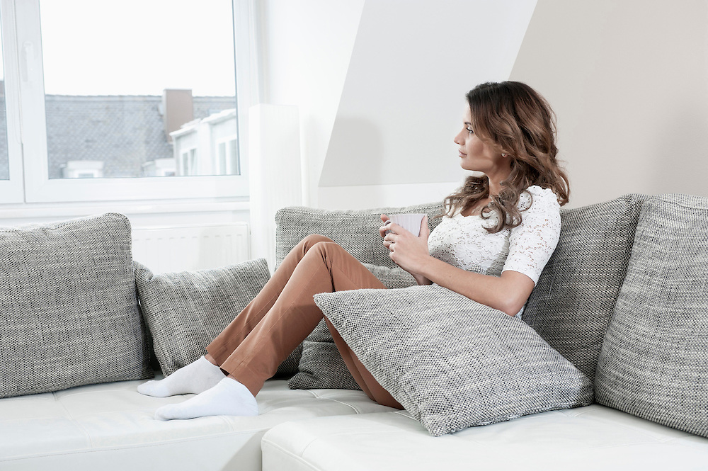 Portrait of young woman relaxing on couch at home