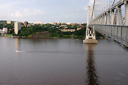 Highland, N.Y. - A boat heads up the Hudson River after passing underneath the Mid-Hudson Bridge between Highland and Poughkeepsie on July 8, 2006. Poughkeepsie is in the background. ©Tom Bushey