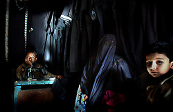 """A Muslim Kashmiri woman sits inside a shop with her children where traditional Islamic veils are made in Srinagar, the summer capital of Indian held Kashmir. The shadowy group, Lashkar-e-Jabbar, also known as Allah's Army sent a letter to a local newspaper saying that Muslim Kashmiri women must adhere to the dress code or face acid attacks beginning on April 1, 2002. The leader of the group also wrote, """"if our members see any boy or girl or any illegal couple doing acts of immortality they will be killed there and then"""".The same group claimed responisiblity for two acid attacks on women in Srinagar last year. Kashmir has been the center of the ongoing dispute between India and Pakistan since the region was partioned when the British left in 1947."""