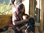 An Akha Cherpia ethnic minority woman sews traditonal clothing whilst breastfeeding her baby son in Ban Nam Sa village, Phongsaly province, Lao PDR. One of the most ethnically diverse countries in Southeast Asia, Laos has 49 officially recognised ethnic groups although there are many more self-identified and sub groups. These groups are distinguished by their own customs, beliefs and rituals. Details down to the embroidery on a shirt, the colour of the trim and the type of skirt all help signify the wearer's ethnic and clan affiliations.