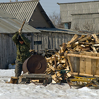In Snopa village, north of the Arctic Circle in Russia, a man chops wood to heat his family's home.