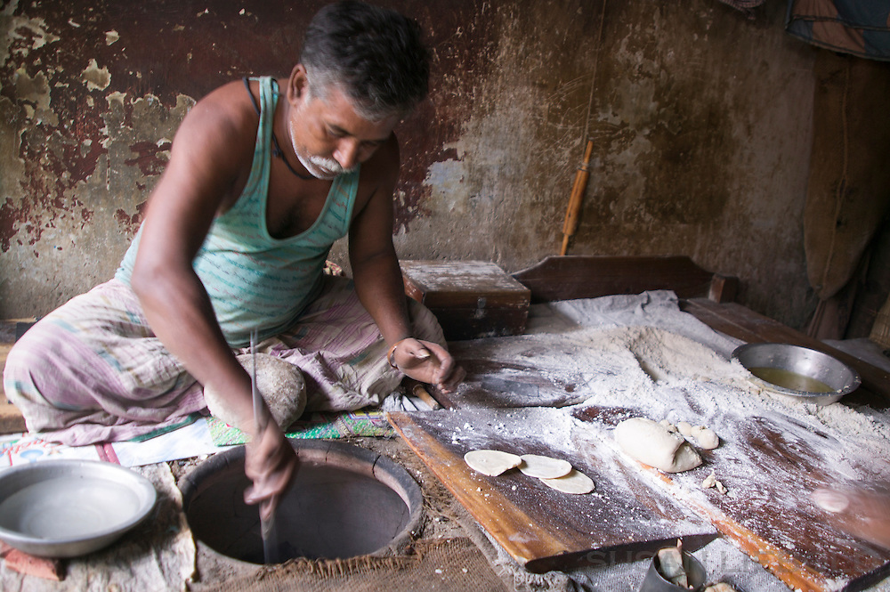 A man making chapatis in a traditional hot oven in Dhaka, Bangladesh.
