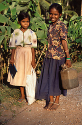 Girl walking home from school with mother in Tamil Nadu; India,