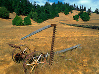 Rusting old mowing machine abandoned in a field near Comptche in Mendocino County California