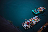 Women row their boats in Ha Long Bay, Vietnam. The women sell goods to tourists traveling on cruises in the bay.