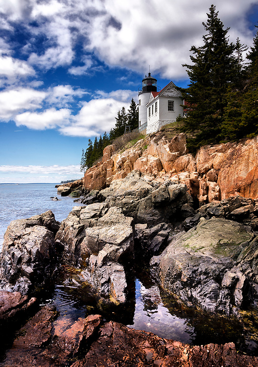 SUBJECT: Lighthouse, Bass Harbor Head, Maine.       IMAGE: The dramatic and vibrant textures and colours of the rocks are echoed in the clouds. The lighthouse is caught between these natural features and the waves below. This is at times a dangerous coast. The strong colours and craggy features are emphasized here to reflect this reality.
