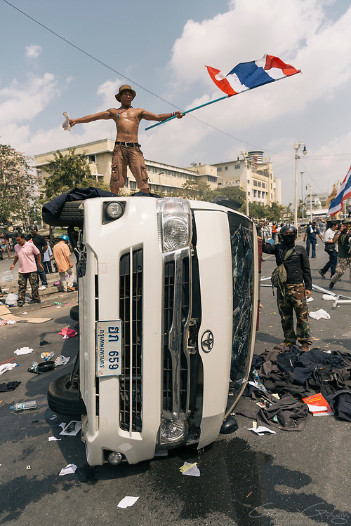 An anti-government protesters carrying a Thai flag stands on top of an overturned ambulance following clashes between demonstrators and police.