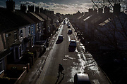 A man walks across Star road, Peterborough, Cambridgeshire. UK