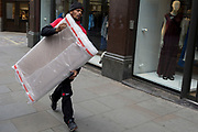A courier with dpd carries a package wrapped in bubble wrap along Long Acre near Covent Garden, on 2nd May 2019, in London, England.