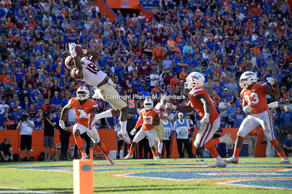 Florida State wide receiver Auden Tate (18) catches a pass in the end zone for a three-yard touchdown in front of Florida defensive back Duke Dawson (7) and linebacker Vosean Joseph (11), second from right, during the second half of an NCAA college football game Saturday, Nov. 25, 2017, in Gainesville, Fla. FSU won 38-22. (Photo by Phelan M. Ebenhack)
