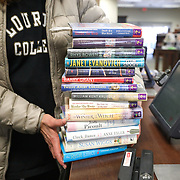 Maumee resident Linda Hoetzl leaves with a stack of books after checking them out at the Maumee Branch Library in Maumee, Ohio, on Friday, March 13, 2020. All Toledo-Lucas County Public Library branches will be closed after March 14 in response to coronavirus. THE BLADE/KURT STEISS