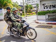 31 OCTOBER 2012 - YALA, YALA, THAILAND: Thai soldiers on security detail for Ok Phansa watch the streets of Yala from a motorcycle during the holiday. Ok Phansa marks the end of the Buddhist 'Lent' and falls on the full moon of the eleventh lunar month (October). It's a day of joyful celebration and merit-making. For the members of Wat Kohwai, in Yarang District of Pattani, it was a even more special because it was the first time in eight years they've been able to celebrate Ok Phansa. The Buddhist community is surrounded by Muslim villages and it's been too dangerous to hold the boisterous celebration because of the Muslim insurgency that is very active in this area. This the year the Thai army sent a special group of soldiers to secure the village and accompany the villagers on their procession to Yala, a city  about 20 miles away.  PHOTO BY JACK KURTZ