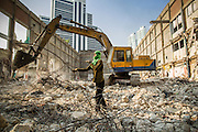 """11 DECEMBER 2012 - BANGKOK, THAILAND:  A worker recycles rebar while heavy equipment demolishes a building at """"Washington Square"""" a notorious entertainment district off Sukhumvit Soi 22 in Bangkok. Demolition workers on many projects in Thailand live on their job site tearing down the building and recycling what can recycled as they do so until the site is no longer inhabitable. They sleep on the floors in the buildings or sometimes in tents, cooking on gas or charcoal stoves working from morning till dark. Sometimes families live and work together, other times just men. Washington Square was one of Bangkok's oldest red light districts. It was closed early 2012 and is being torn down to make way for redevelopment.    PHOTO BY JACK KURTZ"""