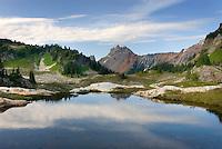 Alpine tarn in basin of Yellow Aster Butte, American Border peak in the distance (2437 meters 7995 feet), Mount Baker Wilderness Washington USA beauty in nature