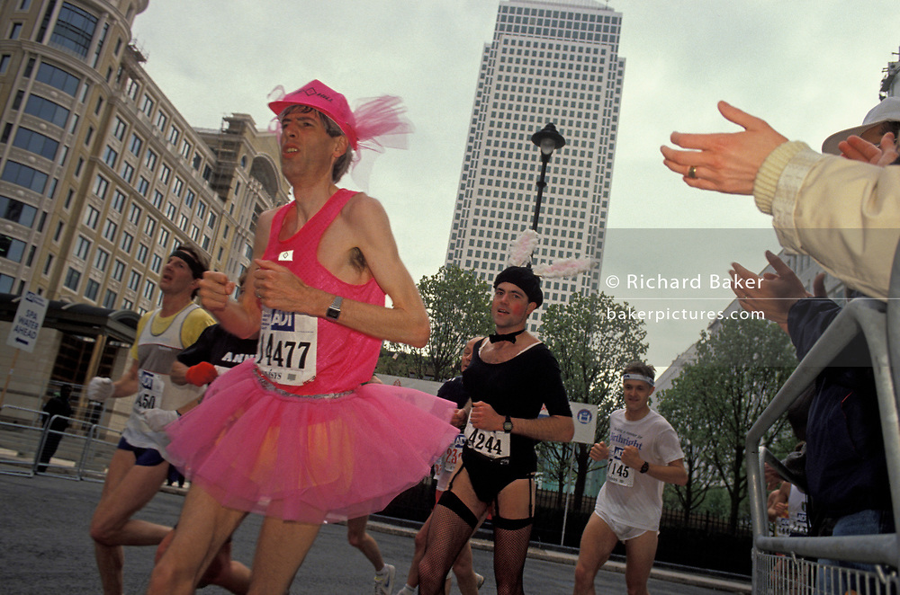 London Marathon runners wearing fancy dress costumes - including a skinny pink ballerina and a Playboy Bunny, pass through the Canary Wharf development in 1991, on 21st April 1991, in London, England. Canary Wharf is the product of the 1980s financial boom when during the term of Prime Minister Margaret Thatcher, huge building projects such as the Docklands consortium saw vast changes in London's landscape.