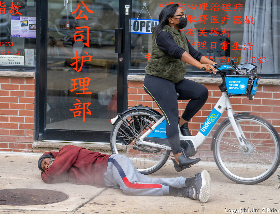 A homeless man huddles near a manhole cover to gather warmth from the rising steam as the world passes him by in Chinatown, Philadelphia, PA.
