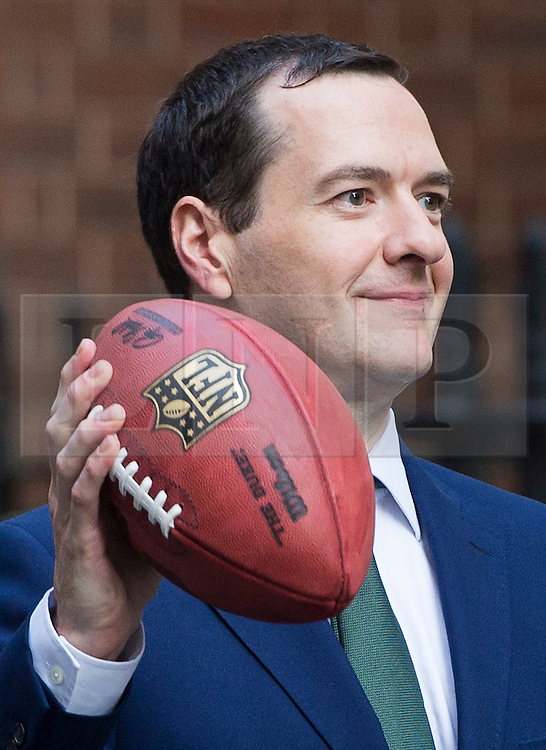 © Licensed to London News Pictures. 02/10/2015. London, UK. British chancellor GEORGE OSBORNE throwing an american football with Dan Marino (not pictured) and Curtis Martin (not pictured) after meeting with NFL team owners, execs and former stars at Downing Street ahead of this weekend NFL game at Wembley stadium.  Photo credit: Ben Cawthra/LNP