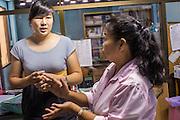28 MARCH 2013 - BANGKOK, THAILAND: Michelle Kao (left) talks to Dachanee Ariso (nickname, Kaew) in the Thai Peace Foundation office.     PHOTO BY JACK KURTZ
