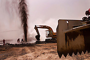 """A Boots and Coots team member directs a backhoe clearing debris away from a gushing oil well minutes after the fire was extinguished. The ground is still smoking. The well was capped two hours later using a """"stinger,"""" a tapered pipe on the end of a long steel boom controlled by a bulldozer. Drilling mud, under high pressure, was pumped through the """"stinger"""" into the well, stopping the flow of oil and gas. Rumaila is also spelled Rumeilah."""