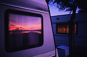 """Europe, France, Camargue, Saintes Maries de la Mer. Sunset reflected in a caravan window. The Gypsy festival """"le Pelerinage des Gitans aux Saintes Maries de la Mer"""" takes place every year in mid May. Gypsies arrive from all over Europe a few weeks before the main festival days, the 24th and 25th May.  The pilgrimmage is Catholic but many Gypsies, Manouche, Gitans, Roma come to see their patron 'Saint Sara' and for the festival atmosphere, the yearly gathering of friends, the music and dance. Gypsies are still regarded with much distrust and racism, they are not liked by the shopkeepers but are well treated by the gentry, especially the Baroncelli family who were instrumental in making this officially a Gypsy festival. One Hundred years ago the Gypsies were not allowed into the church, as it is they still have to camp outside the town."""