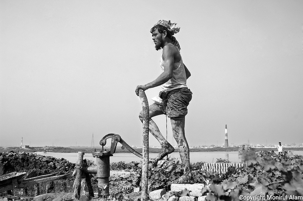 Dhaka. Bangladesh. A man pumping water in the brick field. Bangladesh ranks first as the nation most vulnerable to the impacts of climate change. Scientists expect rising sea levels to submerge 17 percent of Bangladesh's land and displace 18 million people in the next 40 years.
