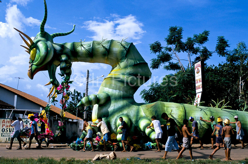 """A oversized Caterpiller leaves the warehouse to enter the """"Bumbodromo"""", the stadium where the """"Boi Bumba"""" Carnival takes place, Parintins, Brazil. The carnival serves to celebrate and re-enact Indian traditions and perpetuate myths and legends. It has evolved over time and involves the battle between to opposing bulls, known as Garantido and Caprichoso."""