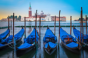 """Moored gondolas at Piazza San Marco in Venice, Italy<br /> .....<br /> Venice is a city in northeastern Italy sited on a group of 118 small islands separated by canals and linked by bridges. It is located in the marshy Venetian Lagoon which stretches along the shoreline, between the mouths of the Po and the Piave Rivers. Venice is renowned for the beauty of its setting, its architecture and its artworks. The city in its entirety is listed as a World Heritage Site, along with its lagoon. Venice is the capital of the Veneto region. In 2009, there were 270,098 people residing in Venice's comune. Although there are no historical records that deal directly with the founding of Venice, tradition and the available evidence have led several historians to agree that the original population of Venice consisted of refugees from Roman cities near Venice such as Padua, Aquileia, Treviso, Altino and Concordia (modern Portogruaro) and from the undefended countryside, who were fleeing successive waves of Germanic and Hun invasions. Some late Roman sources reveal the existence of fishermen on the islands in the original marshy lagoons. They were referred to as incolae lacunae (""""lagoon dwellers""""). The traditional founding is identified with the dedication of the first church, that of San Giacomo at the islet of Rialto (Rivoalto, """"High Shore""""), which is said to have been at the stroke of noon on 25 March 421."""
