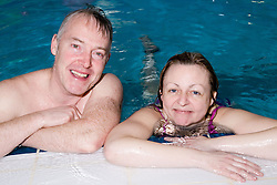 Two people in the swimming pool at their local leisure centre,