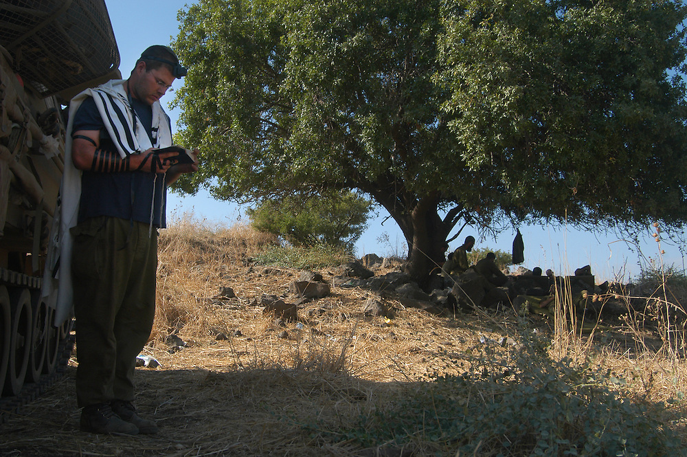 """IDF artillery conservative soldier during his morning prayer - """"shacharit"""" the morning of the cease-fire.<br /> 2nd Lebanon War. Israel, August 2006."""