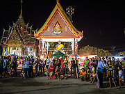 """14 MARCH 2014 - NAKHON CHAI SI, NAKHON PATHOM, THAILAND: People gather in the parking lot at Wat Bang Phra to watch an acrobatic troupe perform at the opening of the temple's tattoo festival. Wat Bang Phra is the best known """"Sak Yant"""" tattoo temple in Thailand. It's located in Nakhon Pathom province, about 40 miles from Bangkok. The tattoos are given with hollow stainless steel needles and are thought to possess magical powers of protection. The tattoos, which are given by Buddhist monks, are popular with soldiers, policeman and gangsters, people who generally live in harm's way. The tattoo must be activated to remain powerful and the annual Wai Khru Ceremony (tattoo festival) at the temple draws thousands of devotees who come to the temple to activate or renew the tattoos. People go into trance like states and then assume the personality of their tattoo, so people with tiger tattoos assume the personality of a tiger, people with monkey tattoos take on the personality of a monkey and so on. In recent years the tattoo festival has become popular with tourists who make the trip to Nakorn Pathom province to see a side of """"exotic"""" Thailand.   PHOTO BY JACK KURTZ"""