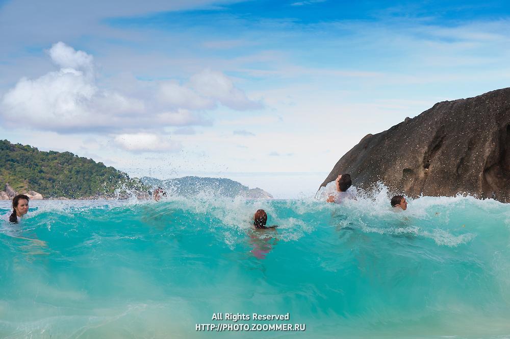Swimmers on a high wave on Ko Bangu, Similan islands, Thailand