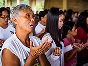 28 JANUARY 2018 - LEGAZPI, ALBAY, PHILIPPINES: People pray during a Catholic mass for evacuees at the evacuation shelter for people from Barangay (community) Matanag in Albay Central School in Legazpi. People from the community have been in the shelter since Mayon volcano started erupting two weeks ago. There are about 500 families at the shelter, around 2,000 people. More than 80,000 people have been evacuated from communities around the volcano and are living in shelters and camps outside of the evacuation zone. The Philippine government is preparing to house the people for up to three months.      PHOTO BY JACK KURTZ