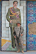Three years after the fall of Baghdad, Saddam's portrait is now a tourists attraction.  Soldiers and contractors pose next to a tile portrait of Saddam Hussein in the courtyard of the former headquarters of the Republican  Guard within the Al Faw Palace Complex in Baghdad, now part of Camp Victory. Tours of the palace are given every Sunday//////Soldier posing next to Saddam Hussein portrait on Camp Victory