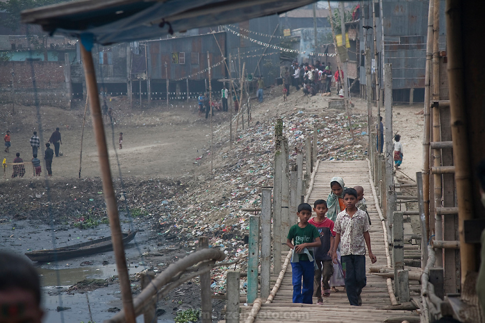 Boys cross a footbridge that straddles a tributary of  the Buriganga river in a slum settlement in the Chairman District of Dhaka, Bangladesh.