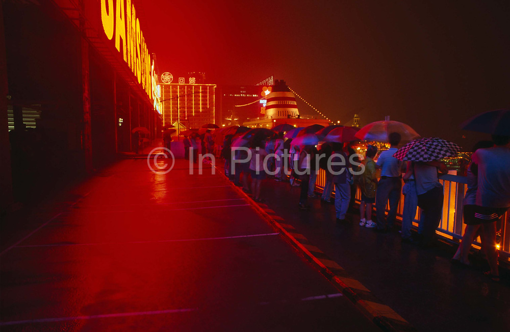 """In heavy monsoonal rain, crowds gather beneath umbrellas on the roof of Ocean Terminal to witness the transfer of sovereignty of Hong Kong from the United Kingdom to the Peoples Republic of China (PRC), often referred to as """"The Handover"""" on June 30, 1997. Midnight signified the end of British rule, and the transfer of legal and financial authority back to China. A cruise liner is moored s small distance away but the glowing red comes from giant advertising lettering on the top floor of the shopping mall which protrudes out into Hong Kong harbour from the Kowloon side of the territory.  Hong Kong was once known as 'fragrant harbour' (or Heung Keung) because of the smell of transported sandal wood."""