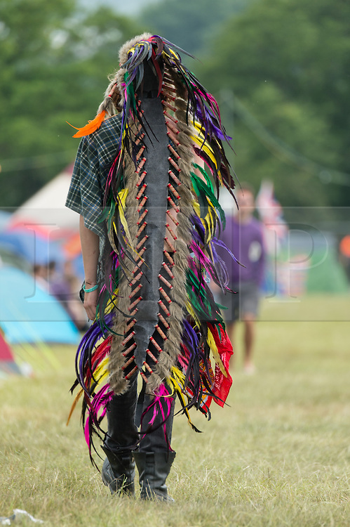 © Licensed to London News Pictures. 12/06/2015. Isle of Wight, UK.  A festival goer wearing an american indian headdress at Isle of Wight Festival 2015 on the morning of Friday Day 2.  Yesterday the weather was hot and Sunny.  Today rain is forecast.  This years festival include headline artists the Prodigy, Blur and Fleetwood Mac.  Photo credit : Richard Isaac/LNP