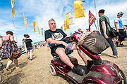 Getting around on a disability scooter. The 2013 Glastonbury Festival, Worthy Farm, Glastonbury. 29 June 2013. © Guy Bell, guy@gbphotos.com, all rights reserved