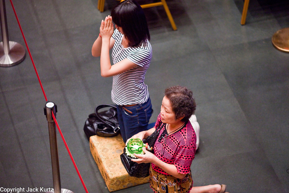 Apr. 28 -- SINGAPORE:  Women pray and make merit in the Buddha Tooth Relic Temple in the Chinatown neighborhood of Singapore. The temple has a tooth from the Buddha. The temple, which opened in 2007, has become one of the most important Buddhist temples in Singapore.     PHOTO BY JACK KURTZ