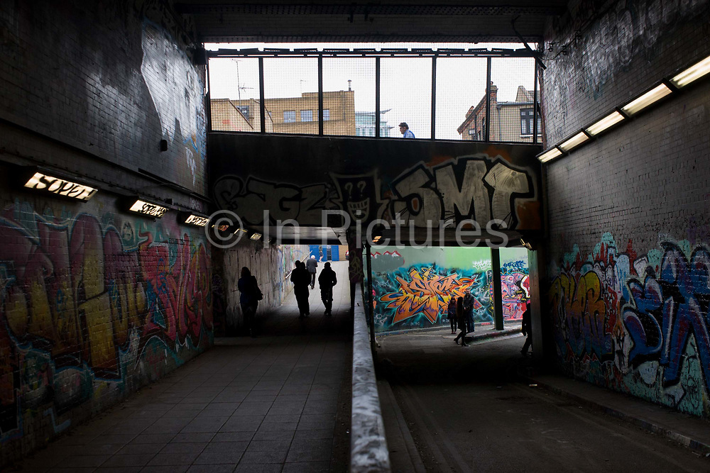 Sinister silhouettes in an underpass tunnel with walls covered with urban graffiti. The tunnel is located near Waterloo mainline station and the concrete bunker-like place has become a favourite landscape for dedicated street artists who are free to cover the walls and pavements (sidewalks) with expressions of their urban artistic ideology and political protest. In daytime, this environment is not as intimidating as it appears and Londoners pass through as a shortcut beneath an otherwise complex route of roadways and railway tracks above. There are also periodic festivals of street art attracting the best of artists including the secretive Banksy.