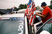 26 SEPTEMBER 2020 - DES MOINES, IOWA: A man attaches a Donald J. Trump flag to his car before a pro-Trump motorcade. More than 1,500 people in 500 vehicles participated in motorcade through Des Moines Saturday. They started in the suburbs south of downtown, drove through downtown, and ended at the State Capitol.       PHOTO BY JACK KURTZ