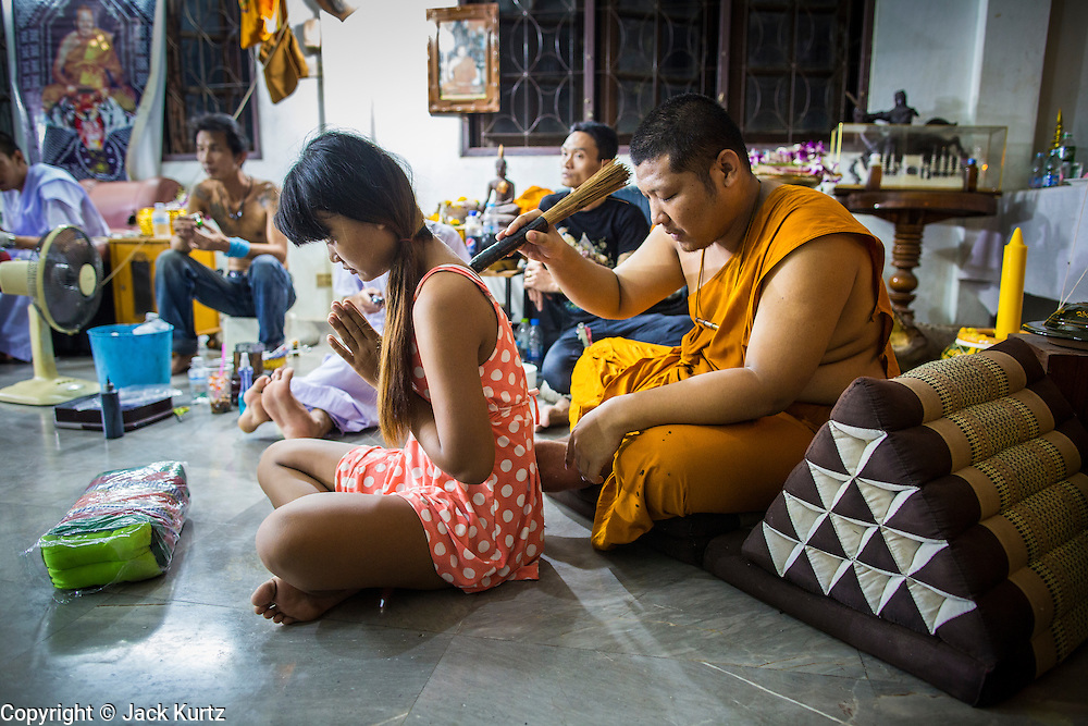 "22 MARCH 2013 - NAKHON CHAI SI, NAKHON PATHOM, THAILAND: A monk blesses a woman's new Sak Yant tattoo at Wat Bang Phra during the tattoo festival. Wat Bang Phra is the best known ""Sak Yant"" tattoo temple in Thailand. It's located in Nakhon Pathom province, about 40 miles from Bangkok. The tattoos are given with hollow stainless steel needles and are thought to possess magical powers of protection. The tattoos, which are given by Buddhist monks, are popular with soldiers, policeman and gangsters, people who generally live in harm's way. The tattoo must be activated to remain powerful and the annual Wai Khru Ceremony (tattoo festival) at the temple draws thousands of devotees who come to the temple to activate or renew the tattoos. People go into trance like states and then assume the personality of their tattoo, so people with tiger tattoos assume the personality of a tiger, people with monkey tattoos take on the personality of a monkey and so on. In recent years the tattoo festival has become popular with tourists who make the trip to Nakorn Pathom province to see a side of ""exotic"" Thailand. The 2013 tattoo festival was on March 23.    PHOTO BY JACK KURTZ"