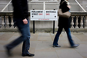 Blurred pedestrians pass the street sign on a Westminster pavement, where Parliament Street becomes Whitehall, the centre for government departments. Walking from left to right the two people whose faces are hidden, step along the pavement where the sign is positioned between the point where the street names change, a few metres from the entrance to Downing Street, the home and office of the UK Prime Minister.