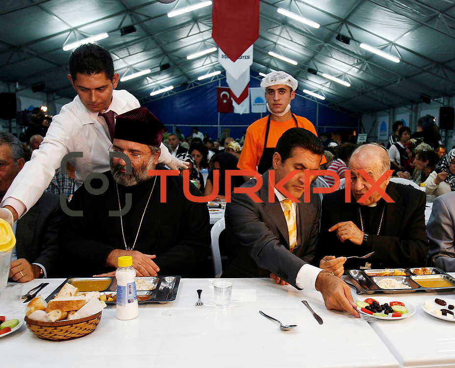 Sisli Mayor Mustafa SARIGUL speak to Catholic Assyrian leader Yusuf SAG on his head as the Turkey's Armenian Patriarch Mesrob II, left, smiles as they chat during an iftar, the evening meal that breaks the daily fast, on the first day of Ramadan in Istanbul, Turkey, Thursday, Sept. 13, 2007. Local Christian leaders joined Muslim worshipper in an iftar meal on the first day of the Islamic fasting month of Ramadan.<br /> Photo by Str./TURKPIX