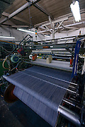 Denim cloth on a loom. Nihon Menpu, Ibara City, Okayama Prefecture, Japan, July 10, 2013. Kojima is the birthplace of Japanese denim and famous for artisan jeans. The area's textile industry is based on advanced dyeing and weaving technology that has it's roots in pre-industrial indigo dyeing.
