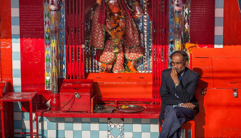 Man sitting at red Hanuman shrine (India)