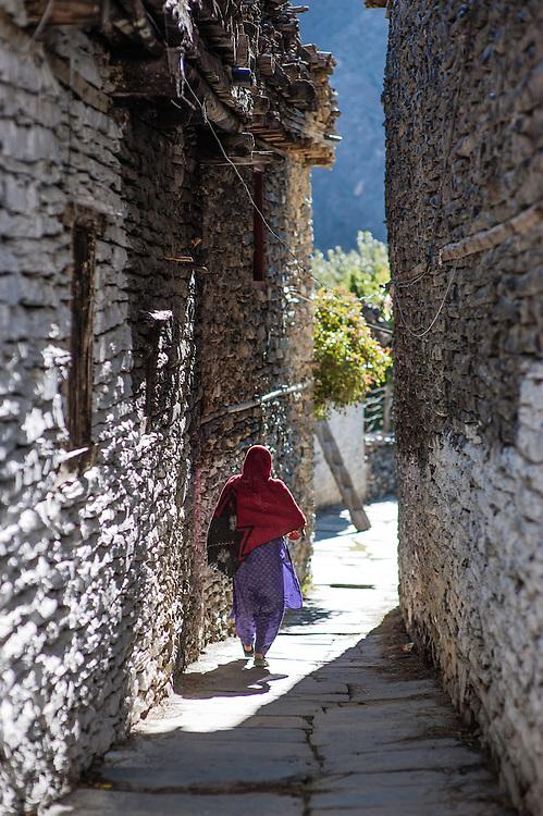Woman walking Marpha stone streets (Nepal)