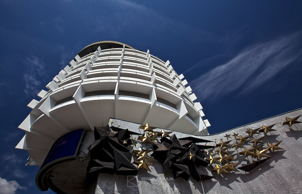 Exterior architectural photograph of Salyut hotel in Kyiv, Ukraine. Daylight with the sun and blue sky, strong shadows and contrast show-up structural elements of the building.