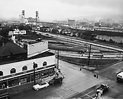 Y-510925A-1.  Looking southwest from North Broadway to North Interstate. Construction of Broadway Bridge ramp. Shows duplexes and homes on East bank waterfront west of Interstate. Kisgans Merchandise Service on North Broadway. Intended to be part of a panorama of Broadway Bridge approach. September 25, 1951