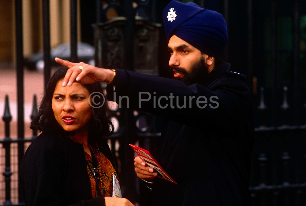 Wearing a turban according to the beliefs of the Sikh faith, a Metropolitan police officer helps an Asian lady citizen outside Buckingham Palace, London England UK. At a time when the 'Met' were recruiting members of ethnic minorities to demonstrate their tolerance of other communities, this man is clearly a symbol of how Britain has changed, since the 1960s to a multi-cultural society. Pointing out direction to help the lady find her way, the officer proudly wears his turban of his religion.