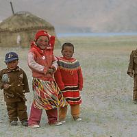 CHINA, Xinjiang Province.  Kyrkyz children outside their family akoi (yurt) near Karakul Lake, Pamir Mountains.